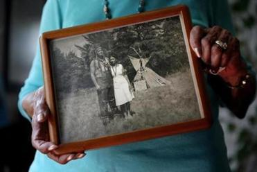 Eleanor Dove held a photograph of herself and her husband Ferris Dove at a Narragansett powwow around 1946.